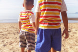 Two baby (brothers) holding hands on the beach by the sea in morning