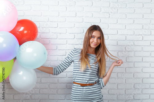 Happy young woman standing over brick wall and holding balloons.