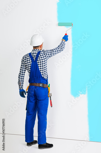 Full length portrait of rear view of painter man painting the wall in blue