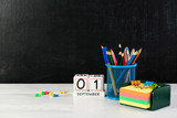 concept of education, the first of September or back to school with school belongings, empty notepad – frame for your text. On the foreground black chalkboard