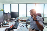 Business investor sitting at his desk in office. - 167777341