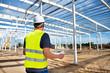 Kierownik budowy hali produkcyjnej stalowej z planem w rękach