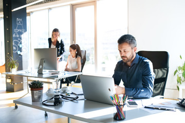 Three business people in the office working together.