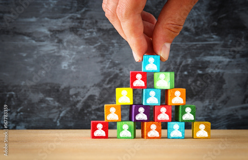 Leinwanddruck Bild man's hand holding a top of wooden blocks pyramid with people icons over wooden table
