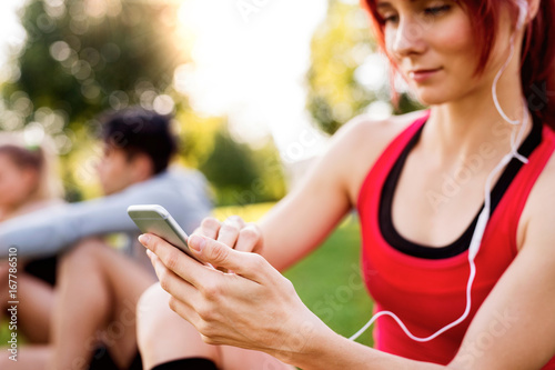 Young athlete in park holding smart phone, listening music.