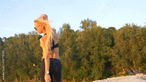 Wall mural Young sport female stands back shaking head with her hair to the wind. Shot in 4k