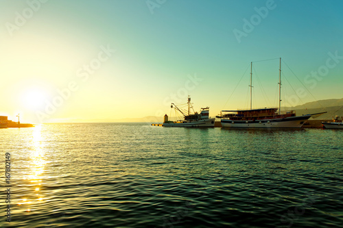Fishing trawler and a sailboat moored in the harbor of a small town Postira - Croatia, island Brac