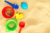 colorful beach toys on sand with copy space