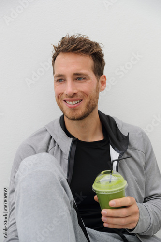 Poster Sap Green smoothie healthy diet man drinking detox vegetable juice cleanse. Sport athlete holding plastic cup drink for morning breakfast.