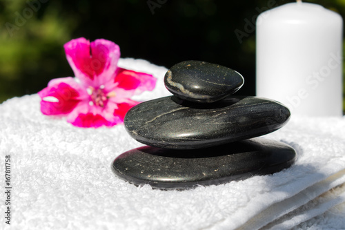 Poster Spa Candles, flowers, stones on a background of greenery for spa massage relaxation