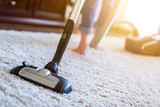 Woman using a vacuum cleaner while cleaning carpet in the house. - 167813572