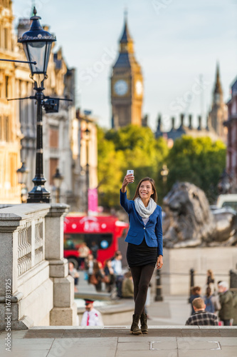London travel tourist taking selfie picture with mobile phone near Big Ben, UK. Business people at Trafalgar Square, United Kingdom. Europe destination vacation. - 167813925