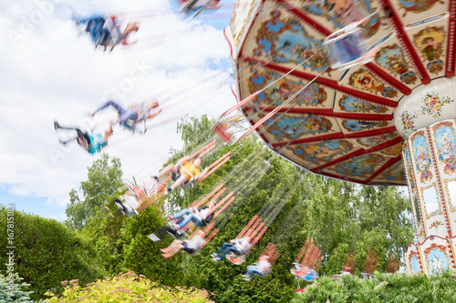 Children swinging on caroussel in theme park on weekend