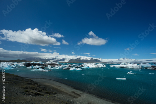 Foto op Canvas Nachtblauw Iceland - Black beach at glacial lake with blue sky and sun over many ice floes