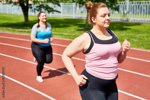 Sticker Active and determined over-sized women jogging on stadium in the morning