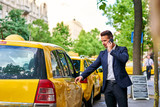 Young businessman walking to a taxi and talking on a phone