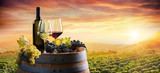 Bottle And WineGlasses On Barrel In Vineyard At Sunset - 167836301