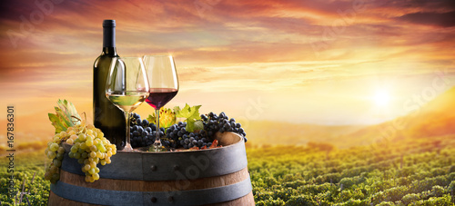 Staande foto Wijngaard Bottle And WineGlasses On Barrel In Vineyard At Sunset