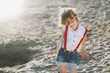 Cute little girl dressed up in hipster clothes and wearing glasses under the sunlight