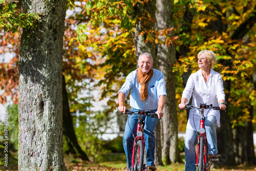 Senior couple, man and woman, on bicycles having bike tour in autumn park