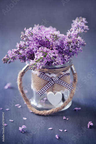 Bouquet of lilacs flowers in a pot decorated with a heart.