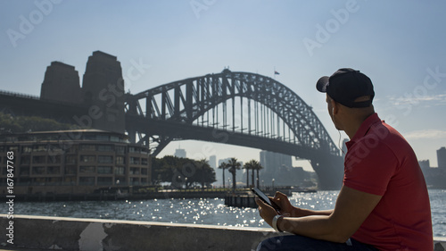 Young casual dressed male looks out to the Sydney Harbour Bridge in Sydney, Australia