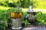 зеленый чай с мятой в стакане на столе в саду - 167848139