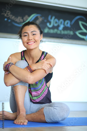 Poster Portrait of smiling yoga woman sitting at yoga mat after workout at yoga studio. Yoga. Woman.