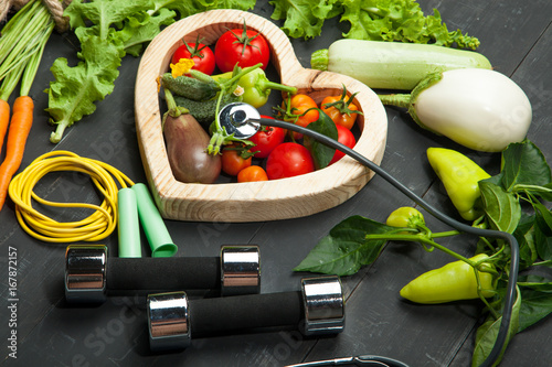 Foto Murales Fresh vegetables. Diet, a healthy lifestyle. Sport, dumbbells and skipping rope on a black background