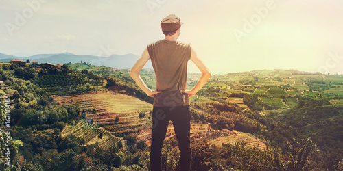 man looking vineyard at sunset, back view of proud person in a beautiful landscape
