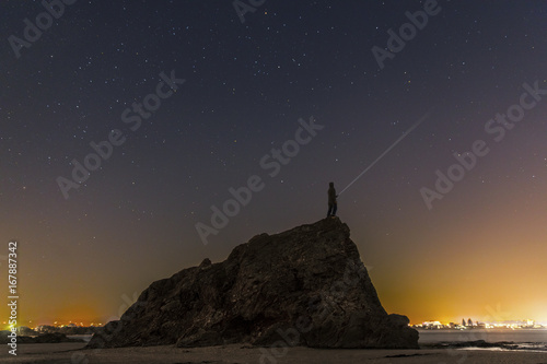 Tuinposter Grijze traf. Silhouette of a person standing on the top of the large Currumbin Rock Gold Coast, shining a torch under a starry night sky.
