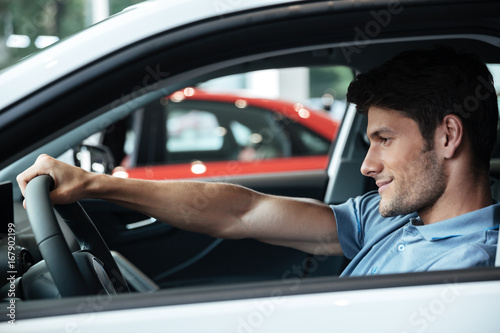 Happy smiling male customer testing his new car