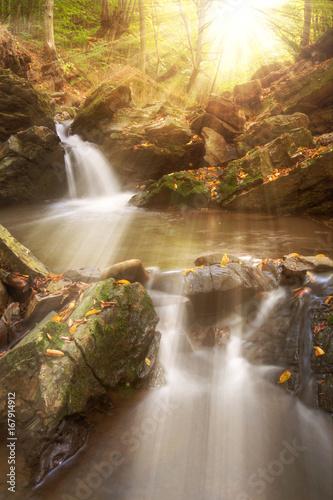 Foto op Aluminium Scandinavië Amazing golden sulight on waterfall in autumn. Autumn waterfall in mountains with golden sunlight.