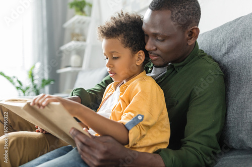 cute african-american father and son reading book together