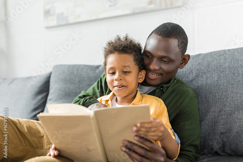 smiling african-american father and son reading book together
