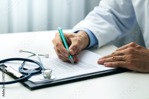 doctor writing documents at desk in clinics office - 167922561