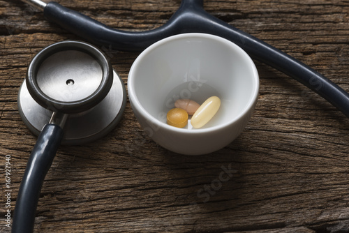 Pills in a container and stethoscope