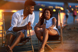 Young mixed race couple sitting and relaxing  at the beach on beautiful evening.They sitting on the sunbeds and drinking bear.