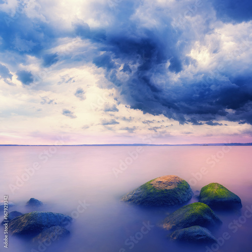 Landscape with stones in water over stormy sky