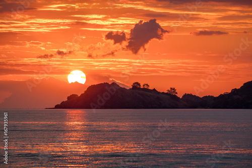 Fotobehang Baksteen Beautiful golden orange sunset over the ocean. The sun sets turning the sky yellow, orange & red tones & reflects in the ocean.