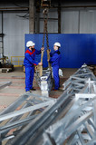 Two workers in white construction helmets load industrial products on the hook of the crane against the background of production