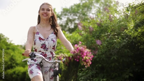 happy young woman riding fixie bicycle in summer