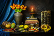 Classic still life with beautiful tulip flowers placed with fresh mangoes,pumpkins,lemon,crab,mussels,illuminated candle,old books and pipe on vintage background