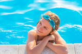 The girl swims in the pool with glasses for swimming. - 167961100