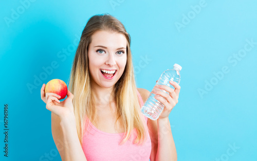 Happy young woman holding an apple and a water bottle on blue background