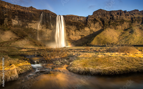 The Seljalandfoss water fall and a small water fall face to sunset with the brown grass in Iceland.