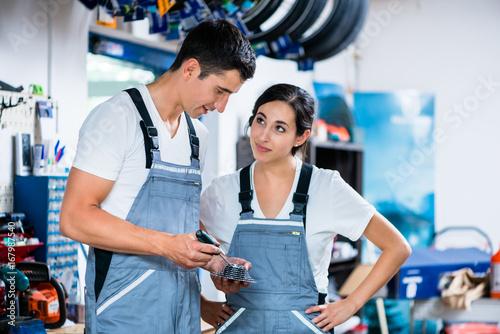 Woman and man as bike mechanics in workshop reparing