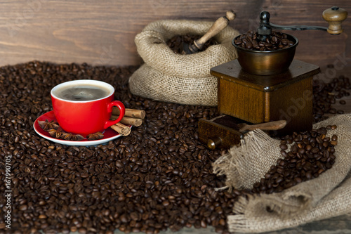 Fotobehang Koffiebonen Coffee, cappuccino or espresso smoke and cinnamon sticks on a wooden table with a coffee grinder