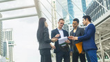 team of five business people smart man and woman talk and present the project work with the paper work on the hand  in good feeling at outdoor pedestrian walk way the city space modern building