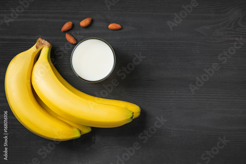 Fotobehang Milkshake A banch of bananas with almonds and milk on wooden background.
